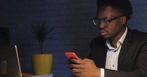 Junger Geschäftsmann, der Smartphone an seinem Schreibtisch im Nachtbüro verwendet stock video