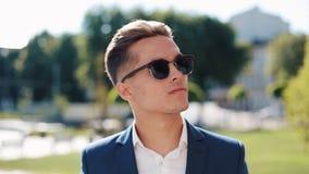 Junger Geschäftsmann in der Sonnenbrille seitlich, die draußen schaut stock video