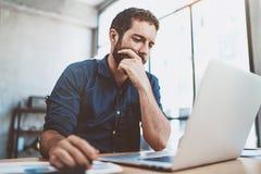 Junger Geschäftsmann, der am sonnigen Arbeitsplatz auf Laptop beim Sitzen am Holztisch arbeitet Unscharfer Hintergrund horizontal stockfotos