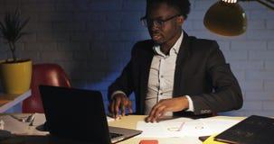 Junger Geschäftsmann, der spät an Laptop im Büro nachts arbeitet Er liest das arbeiten der guten Nachrichten und der Ende stock video