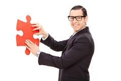 Junger Geschäftsmann, der Stück eines Puzzlespiels hält Stockbilder