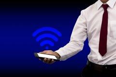 Junger Geschäftsmann, der Touch Screen des Smartphone 3D mit Ikone Technologie wifi hält stockfotos