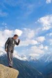 Junger Geschäftsmann, der unten von der Gebirgsspitze schaut Stockfotografie