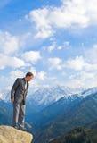 Junger Geschäftsmann, der unten von der Gebirgsspitze schaut stockbilder