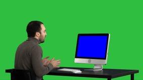 Junger Geschäftsmann, der Videoanruf auf seinem Computer auf einem grünen Schirm, Farbenreinheitsschlüssel macht Blue Screen-Mode stock footage