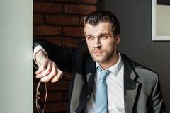 Junger Geschäftsmann, der weg durchdacht schaut Lizenzfreie Stockfotos