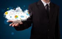 Junger Geschäftsmann, der Wolke mit Diagrammen darstellt Stockfotografie