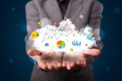 Junger Geschäftsmann, der Wolke mit Diagrammen und Diagrammikonen a darstellt Stockbilder