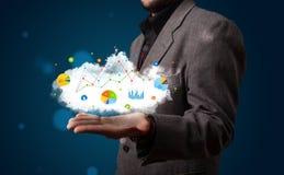 Junger Geschäftsmann, der Wolke mit Diagrammen und Diagrammikonen a darstellt Stockfotografie