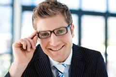 Junger Geschäftsmann, der zum Kamera tragenden gl schaut Stockbild