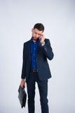 Junger Geschäftsmann in einer Klage sprechend am Telefon Stockfoto