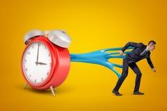 Junger Geschäftsmann festgehalten an rotem Wecker mit blauem klebrigem Schlamm auf gelbem Hintergrund lizenzfreies stockfoto