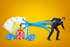 Junger Geschäftsmann festgehalten an Spielkarten und Kasinochips mit blauem klebrigem Schlamm auf gelbem Hintergrund lizenzfreie stockfotos