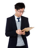 Junger Geschäftsmann gelesen auf dem Klemmbrett stockfotos
