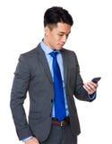 Junger Geschäftsmann gelesen auf dem Mobiltelefon stockfotografie