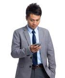 Junger Geschäftsmann gelesen auf Mobiltelefon lizenzfreie stockfotografie