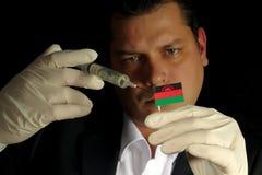 Junger Geschäftsmann gibt eine Finanzeinspritzung zu Malawi-Flagge, die auf schwarzem Hintergrund lokalisiert wird Lizenzfreie Stockbilder
