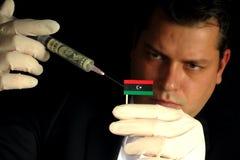 Junger Geschäftsmann gibt eine Finanzeinspritzung zur libyschen Flagge, die auf schwarzem Hintergrund lokalisiert wird Stockfoto