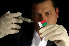 Junger Geschäftsmann gibt eine Finanzeinspritzung zur madagassischen Flagge, die auf schwarzem Hintergrund lokalisiert wird Stockbilder