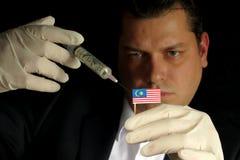 Junger Geschäftsmann gibt eine Finanzeinspritzung zur malaysischen Flagge, die auf schwarzem Hintergrund lokalisiert wird Lizenzfreie Stockfotos