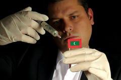 Junger Geschäftsmann gibt eine Finanzeinspritzung zur maledivischen Flagge, die auf schwarzem Hintergrund lokalisiert wird Lizenzfreie Stockfotos