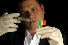 Junger Geschäftsmann gibt eine Finanzeinspritzung zur malischen Flagge, die auf schwarzem Hintergrund lokalisiert wird Stockfotografie