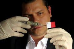 Junger Geschäftsmann gibt eine Finanzeinspritzung zur maltesischen Flagge, die auf schwarzem Hintergrund lokalisiert wird Lizenzfreies Stockbild
