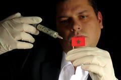 Junger Geschäftsmann gibt eine Finanzeinspritzung zur marokkanischen Flagge, die auf schwarzem Hintergrund lokalisiert wird Stockfotografie
