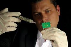 Junger Geschäftsmann gibt eine Finanzeinspritzung zur mauretanischen Flagge, die auf schwarzem Hintergrund lokalisiert wird Stockbild