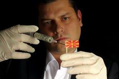Junger Geschäftsmann gibt eine Finanzeinspritzung zur mazedonischen Flagge, die auf schwarzem Hintergrund lokalisiert wird Stockfotos