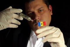 Junger Geschäftsmann gibt eine Finanzeinspritzung zur Moldovan Flagge, die auf schwarzem Hintergrund lokalisiert wird Lizenzfreie Stockbilder