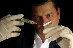 Junger Geschäftsmann gibt eine Finanzeinspritzung zur ungarischen Flagge, die auf schwarzem Hintergrund lokalisiert wird Stockfotos