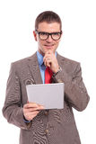 Junger Geschäftsmann hält Tablette und lächelt mit der Hand auf Kinn stockfotos
