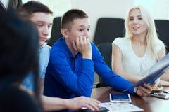 Junger Geschäftsmann hört aufmerksam auf ihre Partner Stockbild