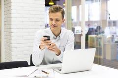 Junger Geschäftsmann am Handy im Büro, sms, Mitteilung Stockfoto