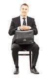 Junger Geschäftsmann im schwarzen Anzug, der einen Aktenkoffer und eine Aufwartung hält Lizenzfreies Stockfoto