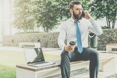 Junger Geschäftsmann im weißen Hemd und in der Bindung sitzt draußen auf Bank, trinkender Kaffee und spricht an seinem Handy Stockfoto