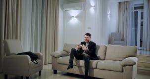 Junger Geschäftsmann kommen zu Hause nach einem Tag der harten Arbeit, den er in ein großes geräumiges Wohnzimmer kommt, das F stock video footage