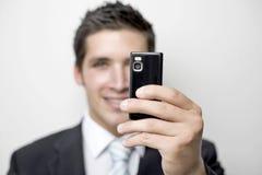 Junger Geschäftsmann macht ein Foto Stockfotografie