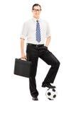 Junger Geschäftsmann mit Aktenkoffer und Fußball unter seinem Fuß Stockfotografie