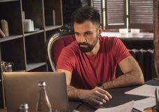 Junger Geschäftsmann mit dem Bart, der bei Tisch mit Laptop im gemütlichen dunklen Büro sitzt Stockbild