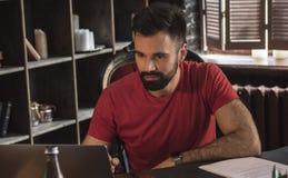 Junger Geschäftsmann mit dem Bart, der im Stuhl sitzt und an Laptop auf Tabelle arbeitet Lizenzfreies Stockfoto