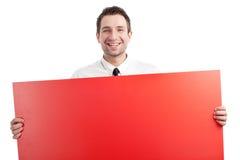 Junger Geschäftsmann mit dem roten unbelegten Zeichenlächeln Lizenzfreies Stockbild