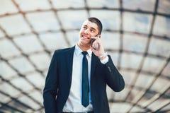 Junger Geschäftsmann mit dem Unterhaltungshandy des Gesellschaftsanzugs im Freien lizenzfreie stockfotos