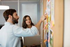 Junger Geschäftsmann mit dem weiblichen Kollegen, der über Diagrammen im Büro sich bespricht Lizenzfreies Stockfoto