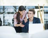 Junger Geschäftsmann mit dem weiblichen Kollegen, der sich bei Tisch über Laptop im Büro bespricht Stockfoto