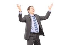 Junger Geschäftsmann mit den angehobenen Händen, die etwas warten zu fallen Stockfoto