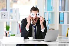 Junger Geschäftsmann mit den gefälschten Augen gemalt auf den Papieraufklebern, die am Arbeitsplatz gähnen stockfoto