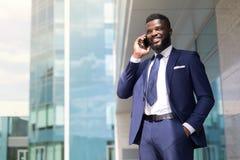 Junger Geschäftsmann mit einem Bart in der blauen Klage, die draußen am Telefon mit Kopienraum spricht lizenzfreie stockfotos