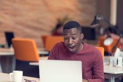 Junger Geschäftsmann mit einem entsetzten Ausdruck, der an einem Laptop arbeitet lizenzfreie stockfotos